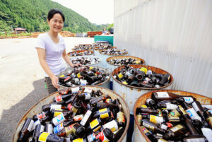 Sonae Fujii of the Zero Waste Academy in Kamikatsu stands next to containers filled with waste