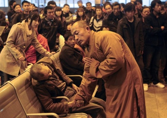 A Buddhist Monk was captured by a photographer that was in a crowd at a train station, blessing a dead man.